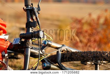 Detail of a mountain bike after ride in nature. Sunny day in the countryside. A bicycle without people on a background of orange leaves. Detaik of the bicycle, flashlight, handlebar and wheel.