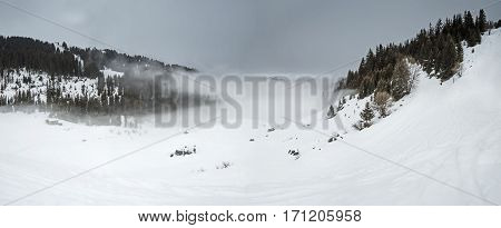 Panoramic View Down A Mountain Valley With Low Clouds And Overcast Sky
