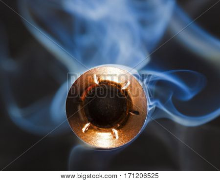 Bullet from a pistol that is a hollow point with smoke behind