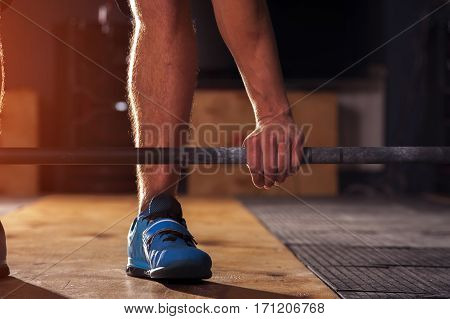 Closeup of male hand holding barbell. Man preparing for dead lift exercise with barbell in gym. Weightlifting, power lifting workout in gym.