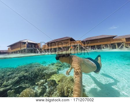 Young man snorkeling underwater on a colorful coral reef of Maldives island.