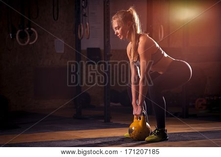 Attractive blonde girl doing exercises with kettlebell. Weightlifting and power lifting workout. Sports, fitness concept.