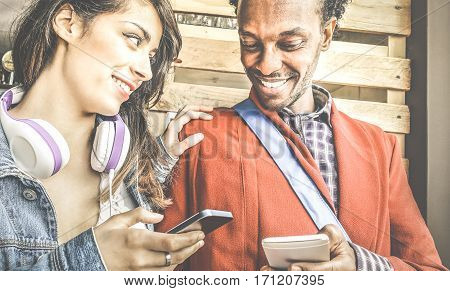Multiracial couple flirting with smartphone numbers - Modern concept of mobile phone technology with happy people having fun - City urban lifestyle - Retro filter with focus on girl