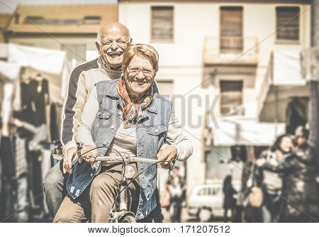 Happy senior couple having fun with bicycle at flea market - Concept of active playful elderly with bike during retirement - Everyday joy lifestyle without age limitation - Contrast desaturated filter