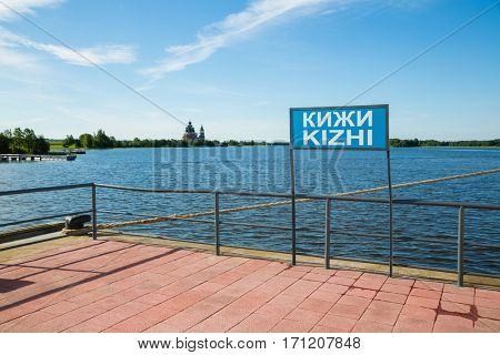 Pier on the famous island of Kizhi in Lake Onega in Karelia in the north of Russia. Inscription on the banner Kizhi on the Russian and English languages.