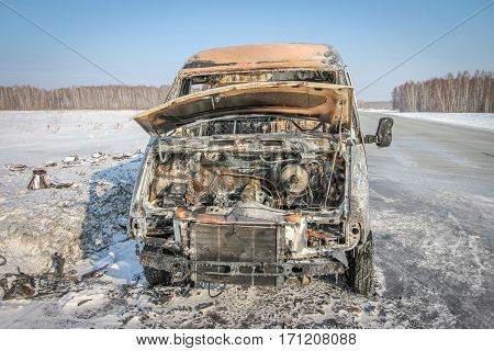 Lonely burnt car on a suburban highway in the winter