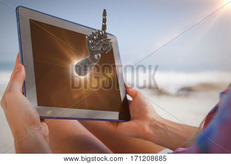 Woman sitting on beach in deck chair using tablet pc against composite image of robotic arm pointing