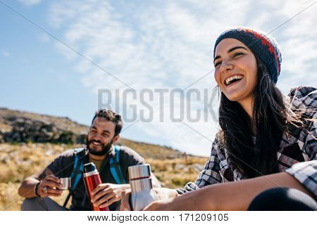 Smiling young woman taking a break during hiking. Cheerful hikers having rest on field
