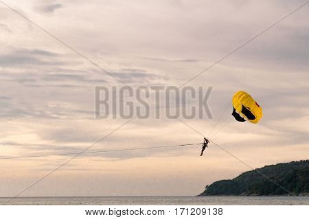 Parachutist on background of golden sunset sky
