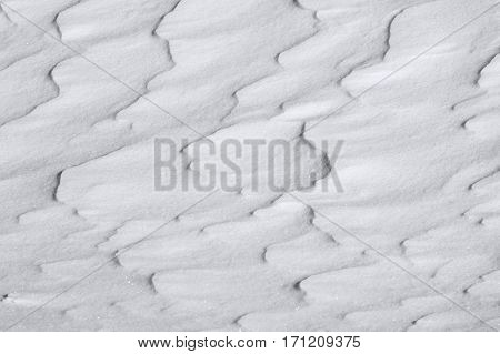 Snow surface wavy pattern, white textured background created by winter wind, nature abstraction