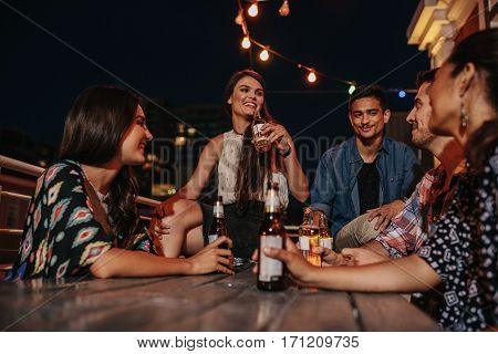 Group of happy young people having a rooftop party at evening. Friends enjoying party with drinks.