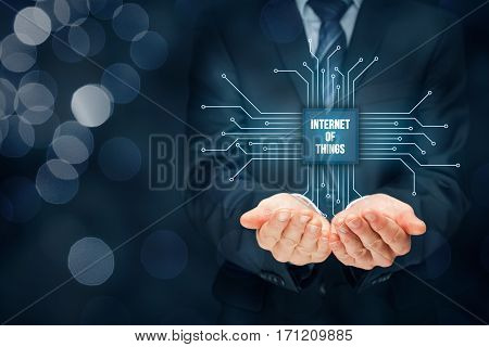 Internet of things (IoT) concept. Businessman offer Internet of Things products and solutions. Abstract chip with text Internet of Things connected with abstract devices represented by points.