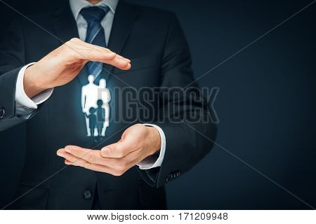 Family life insurance, family services and supporting families concepts. Businessman with protective gesture and silhouette representing young insured family. Left composition.