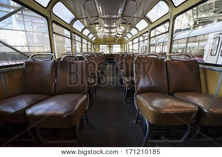Retro bus inside, old public transport interior with leather seats in row, chrome handles for passengers and big windows, vintage vehicle, nostalgia background