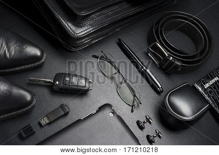 Man accessories in business style, gadgets, eyeglasses, car key, briefcase, shoes and other luxury businessman attributes on leather black background, fashion industry, selective focus