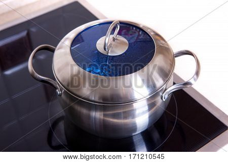 metal pots in the kitchen on induction hob