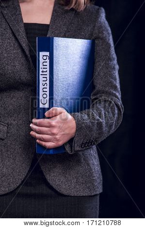 Blue folder with inscription Consulting in female hands. Toned image