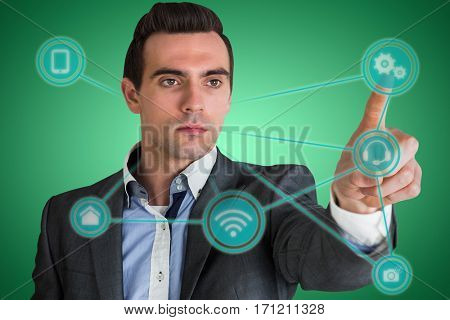Handsome young businessman pointing against green vignette