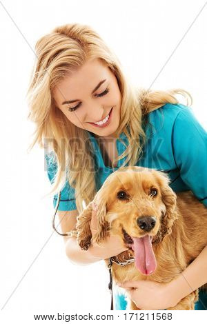 Young smile female veterinarian examinng dog