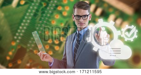 Businessman holding glass sheet and touching invisible screen against green printed circuit board