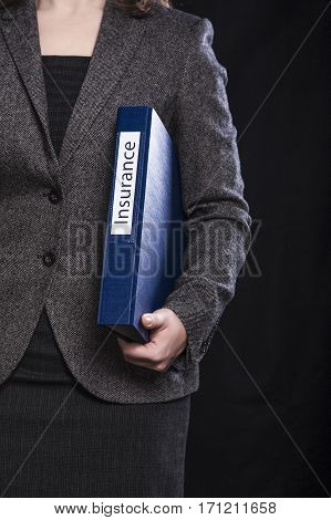 Woman manager with blue documents folder on black background