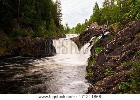 Tourists from the famous waterfall Kivach on the Suna River in Karelia in the north of Russia in the summer