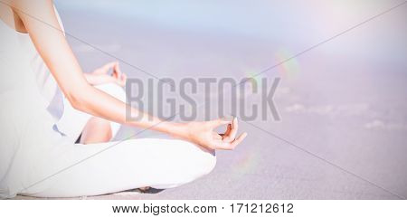 Midsection of woman performing yoga on beach