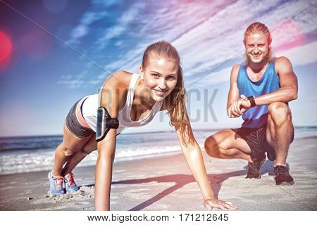 Portrait of couple exercising on sand at beach