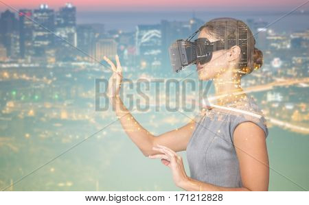Side view of young woman gesturing while using virtual video glasses against high angle view of illuminated cityscape