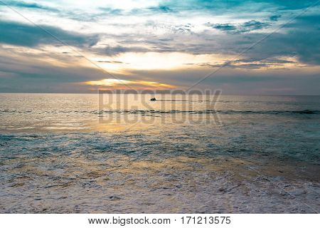 Evening on the sea and the sun gradually disappearing behind the horizon