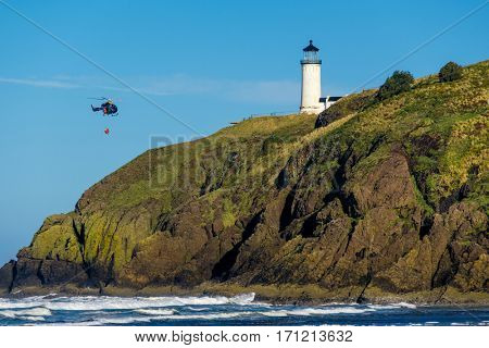 North Head Lighthouse at Pacific coast, Cape Disappointment, built in 1898, WA, USA. Coast guard helicopter in the sky.