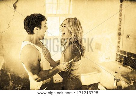 Grey background against happy couple being excited with positive pregnancy test