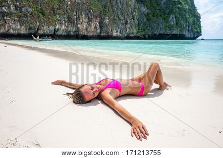Woman wearing pink bikini laying on tropical beach at Thailand with arms outstretched