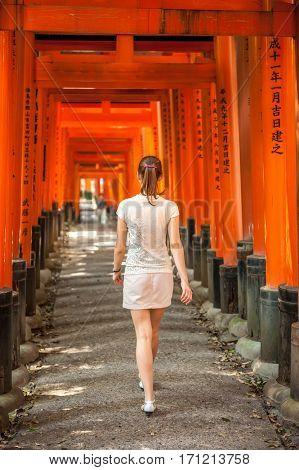 Woman walking through wooden Torii Gates at Fushimi Inari Shrine, Kyoto, Japan