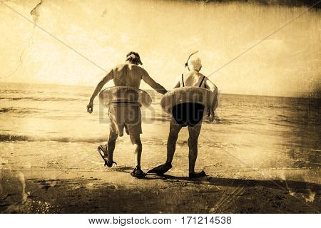 Grey background against senior couple in inflatable ring and flipper walking at beach