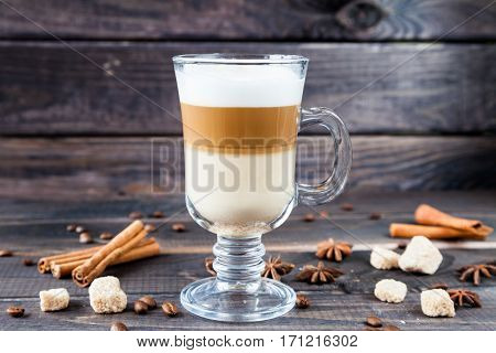 Hot latte macchiato coffee with tasty foam in tall clear glass on dark wooden table serving with cinnamon, cane sugar and roasted coffee beans. Breakfast time. Low key photo.