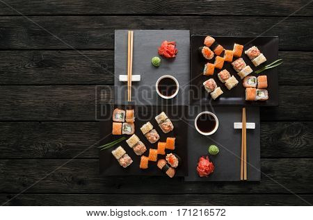 Japanese food restaurant, sushi maki gunkan roll platter. Set for two on black slate plates with chopsticks, ginger, soy, wasabi. Top view with copy space on rustic wood background