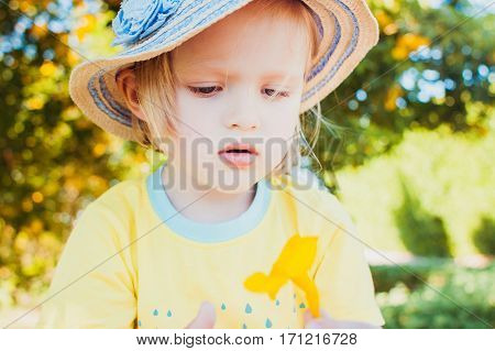 Close-up portrait of cute little girl wearing hat. Summer day. Natural beauty.