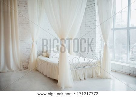 Bedroom in soft light colors. Big comfortable elegant double bed in white brick loft interior with large window.