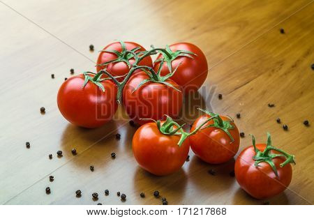 Fresh grape tomatoes with spices for use as cooking ingredients on wooden table. Healthy eating.  copy space