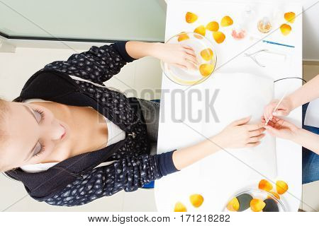 Nail care beauty wellness spa treatment concept. Woman preparing nails before manicure pushing back cuticles using wooden stick