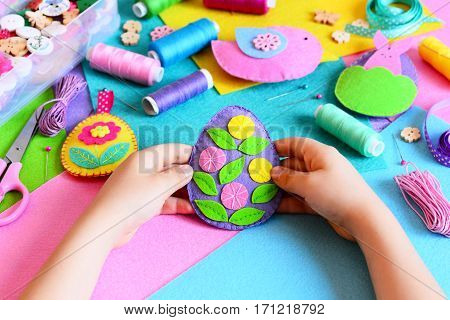 Kid holds Easter egg decor in his hands. Small kid shows his Easter crafts. Colorful felt Easter eggs, bunny and bird decorations, sewing materials and tools on a table. Simple holiday DIY for kids