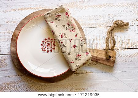 Off-white empty plate with red board on round cutting board linen floral napkin white plank wood background Provence style rural kitchen interior minimalistic kinfolkflat lay top view