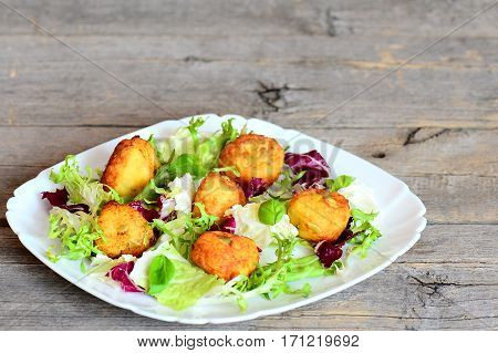 Golden fried mashed potato cutlets with pumpkin seeds served with fresh lettuce mix and basil on a plate. Wooden background with copy space for text. Quick and tasty potato cutlets recipe