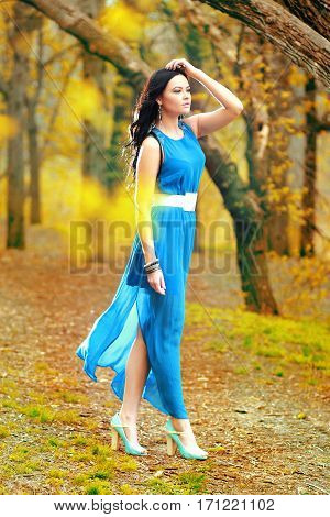 Sensual nymph in autumn garden back side of sexy girl wearing long dress enjoying autumnal nature in the park fashion concept