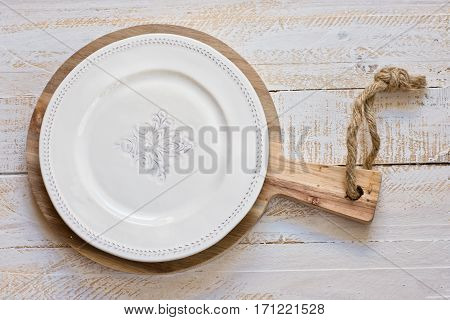 White vintage empty plate on round cutting board white plank wood background Provence style kitchen interior minimalistic kinfolkflat lay copyspace