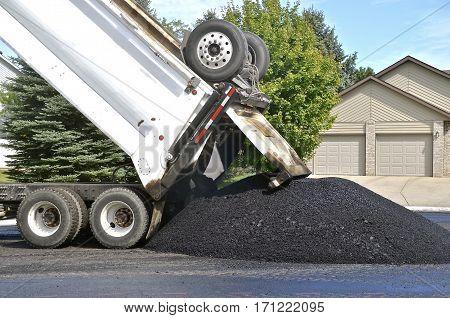 A truck unloads wet asphalt for a street repair project
