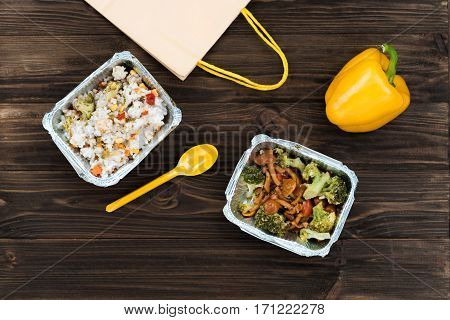 Food delivery. Grey paper-bag with yellow handles is situated near two boxes, stewed rice with vegetables and well-done broccoli with mushrooms are packed in foil boxes lying next to yellow pepper