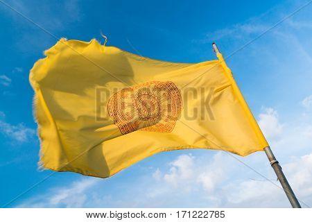 Yellow Buddhist flag against a blue sky.
