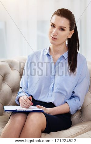 Successful woman. Beautiful positive successful woman holding a pen and making notes while being at work